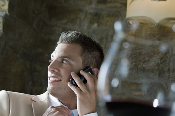 Young man in suit sitting with mobile phone at a restaurant