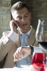 Young man in suit with mobile phone at a restaurant checking time