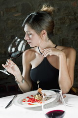 Young woman with plate of food sniffing her wine at restaurant