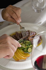 Closeup of young man's hands with knife and fork at his plate