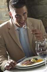 Young man eating with glass of wine at a restaurant