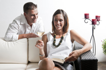 Young man leaning on couch with young woman with book and white wine