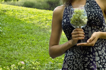 Torso of young woman in vineyard with a wineglass of white grapes