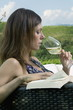 Young woman sitting on couch in vineyard drinking white wine and reading a book