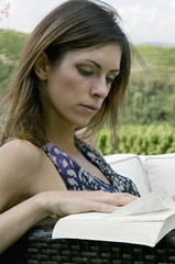 Young woman sitting in vineyard reading a book