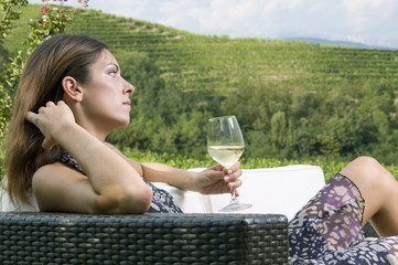 Young woman sitting on couch in vineyard with white wine