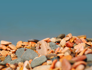 Photo of pebble stones on the sea background, shallow DOF.
