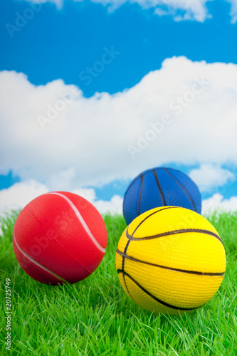 two basketballs and a tennisball on a green lawn against a blue