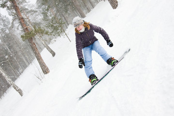 girl rushes down the slope on a snowboard