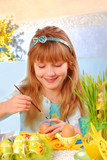 young girl  painting easter eggs