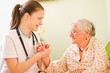 A caring doctor and an elderly sick woman holding hands
