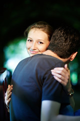 Happy girl in the arms of her fiance in park