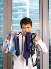 Businessman choosing tie at office