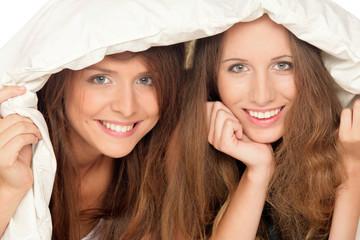 Young girls below duvet