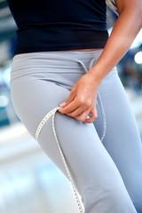 Fit woman measuring her leg