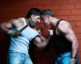 Two muscular angry guys threaten each other