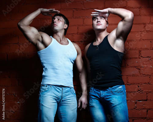 Two muscular guys watching