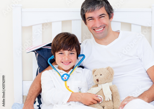 Cheerful father and his sick son playing with a stethoscope