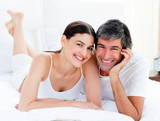 Fototapety Enamored couple embracing lying on their bed