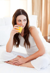 Relaxed woman drinking orange juice on bed