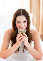 Peaceful woman drinking tea sitting on bed