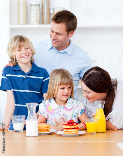 Jolly family eating breakfast in the kitchen