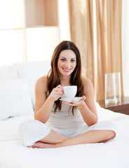 Smiling woman drinking coffee sitting on bed