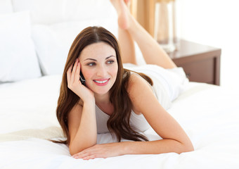 Brunette woman on phone lying on bed