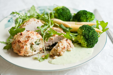 Chicken breast rolls with broccoli and salad on the plate