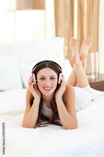 Pretty woman listening music lying on bed