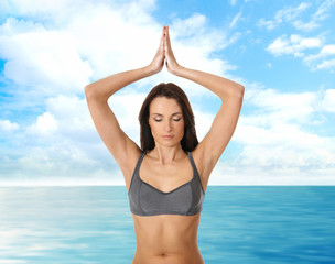 Young beautiful woman doing yoga exercise over sea background