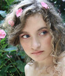 Portrait of a beautiful girl with flowers petals in her hair