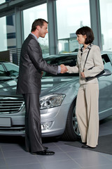 Car salesperson shaking hands with customer at showroom