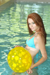sexy woman playing with yellow beach ball in a pool
