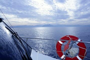 Boat rail with round orange lifesaver blue sea