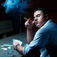 Handsome young gambler smoking