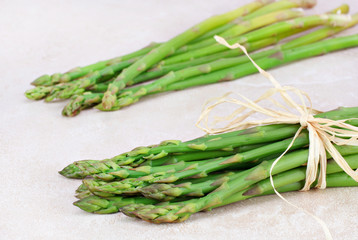 Two bunches of fresh asparagus on tile counter top.