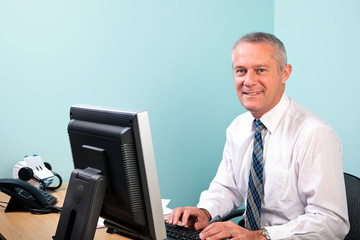 Mature businessman sat at his office desk working
