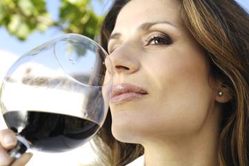 donna che gusta un bicchiere di vino