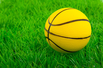 a yellow basketball on a green plastic lawn
