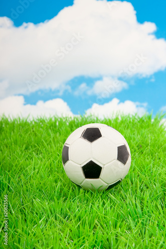 a football on a green lawn against a blue cloudy sky