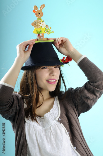 pretty young woman arranging easter bunny on black hat