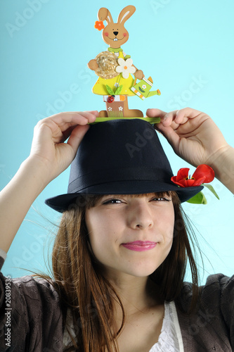 happy girl showing easter bunny on black hat