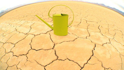 Concept Shot of Watering Can on Baked Dry Earth