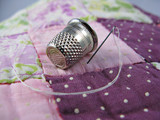 Silver colored thimble on an old antique patchwork quilt poster