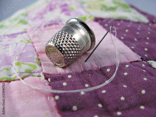 Silver colored thimble on an old antique patchwork quilt