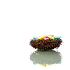 A bird nest full of easter almonds isolated on white