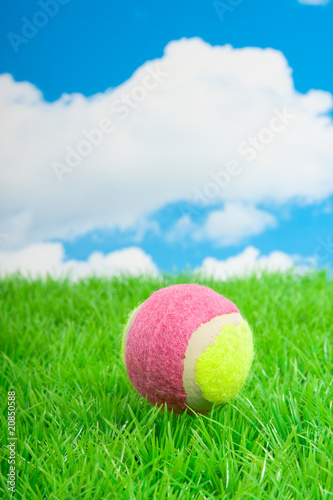 a pink yellow tennis ball on a green plastic lawn against a blue