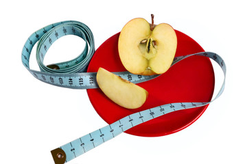 Apple with tape measure on the red plate isolated on white