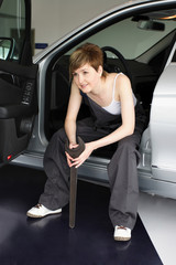 Attractive, friendly auto mechanic checking the engine of a car
